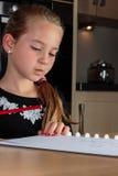 认为的女孩,当做家庭作业在拿着铅笔时的厨房用桌上 库存图片