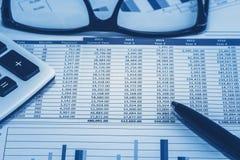 认为的财政银行银行帐户库存报表数据为在蓝色分析的会计与玻璃笔和计算器 免版税库存照片