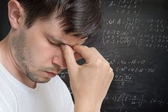 认为的年轻人 解决一道困难的数学题 算术惯例在背景中 免版税库存图片