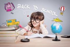 认为逗人喜爱的小女孩学习在图书馆和,学校概念 库存照片