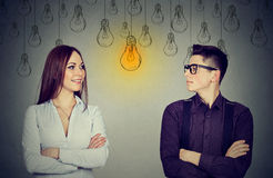 认知技能概念,男性对女性 看电灯泡的男人和妇女 库存图片