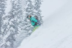 讨便宜者女子的挡雪板在山的粉末雪去下来在降雪 免版税图库摄影