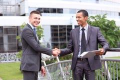 讨论二个的生意人在办公室之外的文件 免版税图库摄影