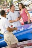讨论汽车的夫妇新的销售人员 免版税图库摄影