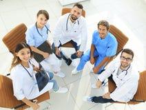 讨论的医护人员现期杂志,坐在书桌后 库存图片