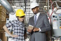 讨论的女性产业工人和男性工程师在木材工厂 图库摄影