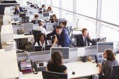 讨论的经理与工友在一个开放学制办事处 免版税库存照片