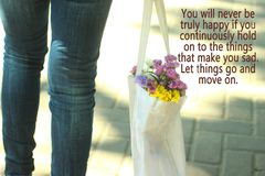 让事继续和移动 与穿牛仔裤的年轻女人腿的概念照片充分运载一个白色袋子色的花 免版税库存照片