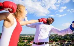 让她的胜利概念 夫妇拳击手套战斗天空背景 女孩确信的力量力量 领导家庭 免版税库存图片