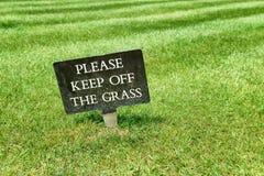 让开在绿色草坪的草标志 免版税库存照片