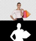 让我们走购物的妇女走与购物带来的,阿尔法通道 库存图片