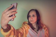 让我采取selfie 拿着智能手机的逗人喜爱的长的卷发女孩采取selfie绿色背景 举行聪明的睡衣的女孩 库存图片