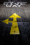 让路在混凝土路绘的黄色箭头 免版税库存图片