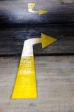 让路在混凝土路绘的黄色箭头 库存图片