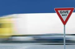让路文本出产量公路交通标志,行动被弄脏的卡车,白色帐篷背景,蓝色夏天天空 图库摄影