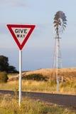 让路标志和风车 免版税库存照片