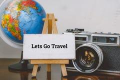 让连同旅行和画架、地球和葡萄酒在木书桌上的照相机布局 选择聚焦射击和退色的作用 库存照片