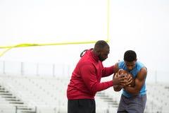 训练一位高中运动员的教练 免版税库存照片