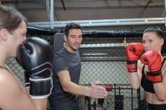 训练与男性教练的两位女性拳击手 免版税库存照片