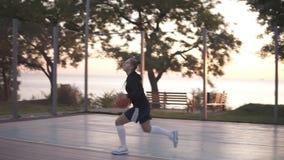 训练和行使户外在地方法院的一个女孩蓝球运动员的Handhelded英尺长度 滴下与 影视素材