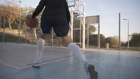 训练和行使户外在地方法院的罕见的观点的一个女孩蓝球运动员 跑与球 股票视频