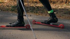 训练四轮溜冰者的一位运动员 在路辗滑雪的两项竞赛乘驾有滑雪杆的,在盔甲 秋天 免版税库存图片