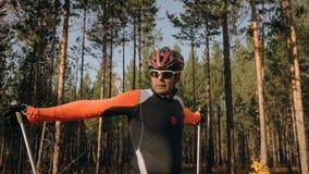 训练四轮溜冰者的一位运动员 在路辗滑雪的两项竞赛乘驾有滑雪杆的,在盔甲 秋天 图库摄影