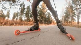 训练四轮溜冰者的一位运动员 在路辗滑雪的两项竞赛乘驾有滑雪杆的,在盔甲 秋天 免版税库存照片