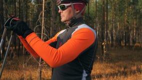 训练四轮溜冰者的一位运动员 在路辗滑雪的两项竞赛乘驾有滑雪杆的,在盔甲 秋天 免版税图库摄影