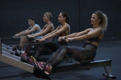 训练在健身房的妇女划船与锻炼机器和拉扯ro 免版税库存照片