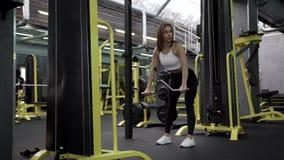 训练在模拟器的亭亭玉立的健身模型背部肌肉 股票录像