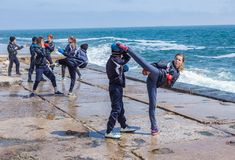 训练在石海岸的孩子空手道 免版税库存照片