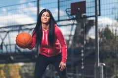 训练户外在一个地方法院的女性蓝球运动员 免版税图库摄影