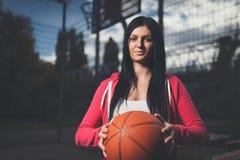 训练户外在一个地方法院的女性蓝球运动员 图库摄影