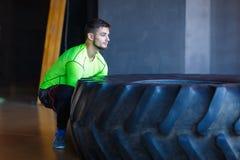 训练有一个重和大轮胎的一个人在健身中心 免版税库存照片