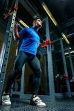 训练的坚强的运动员在健身房,一个人培养一个重的倒钩 免版税库存图片