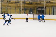 训练的少量男孩在曲棍球棍打 免版税库存图片