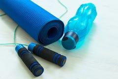 训练的概念和在瑜伽席子的一条跳绳旁边休息瓶或水 免版税库存图片