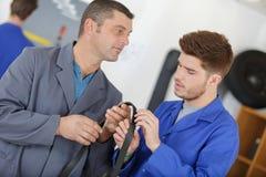 训练老师帮助的学生是汽车修理师 免版税库存图片