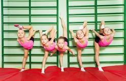 训练体操的女孩在镶嵌墙上的梯子附近 库存照片