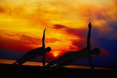 训练和思考在战士姿势的瑜伽人外面由海滩在日出或日落 库存照片