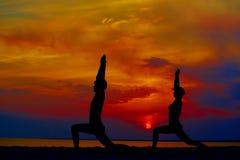 训练和思考在战士姿势的瑜伽人外面由海滩在日出或日落 图库摄影