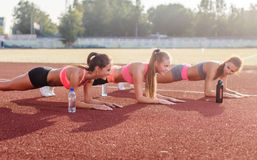 训练在一个晴天的运动小组妇女做铺板锻炼在体育场内 免版税图库摄影