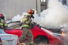 训练在一辆灼烧的汽车的消防员 库存照片