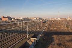 训练在与典型的大厦的在背景的铁路和muontains Lingotto区 都灵 意大利 免版税图库摄影