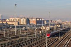 训练在与典型的大厦的在背景的铁路和muontains Lingotto区 都灵 意大利 库存照片