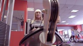 训练在健身俱乐部、健身房和体育活动的人们 有解决与重量的个人教练员的少妇 股票视频