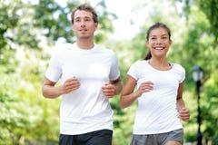 训练在夏天城市的愉快的夫妇赛跑者停放 免版税库存图片