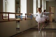 训练在窗口附近的年轻美丽的芭蕾舞女演员 库存图片