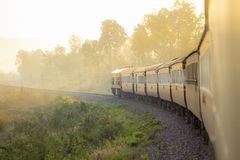 训练在铁轨早晨在countrysi的秋天有雾的 免版税库存图片